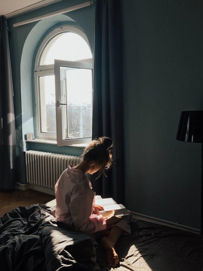Frau liest Buch in Vorbereitung auf Yoga-Ausbildung