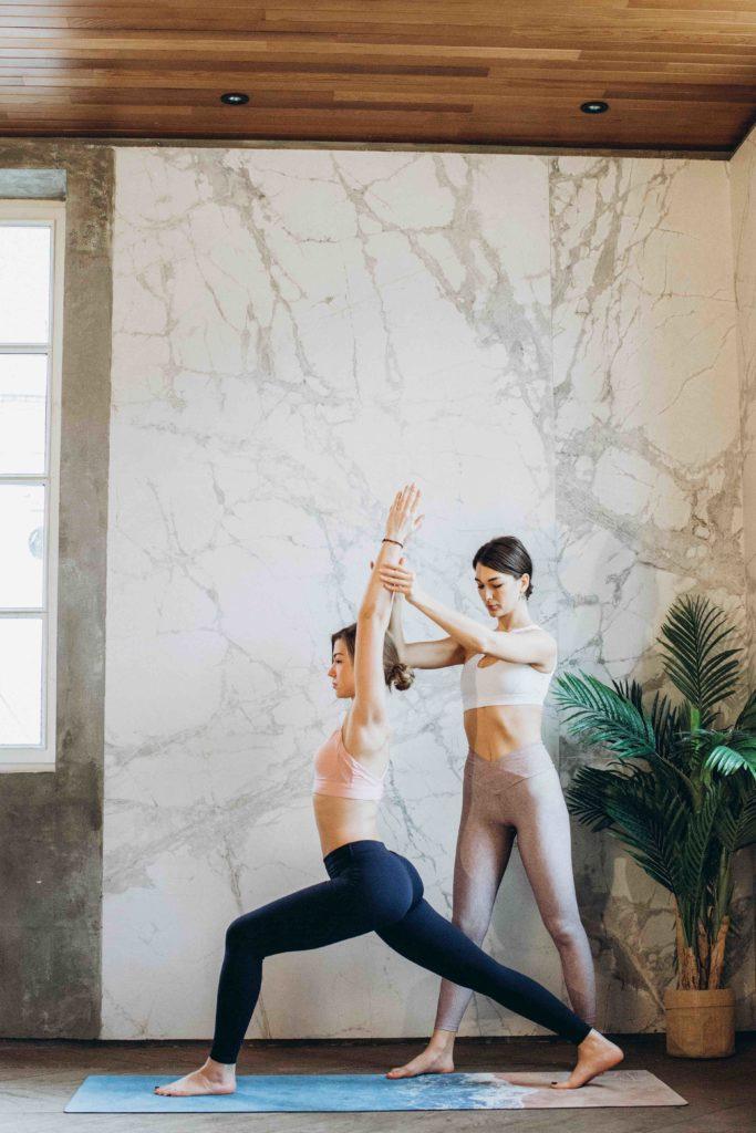 Yogalehrerin hilft einer Schülerin